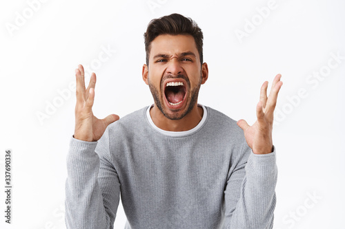 Fotografiet Angry and disappointed handsome bearded man in grey sweater swearing and cursing
