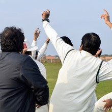 Cheerful Cricketers Celebrating Their Victory, Smiling Cricket Players Celebrating Win At Field Against Clear Sky