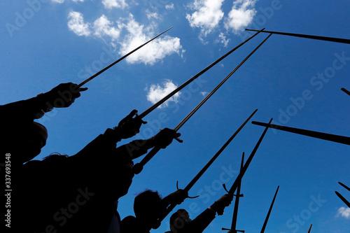Silhouette di spase elevate dai cavalieri verso il cielo, isolate su sfondo blu Canvas Print