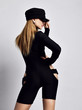 Young beautiful slim blond woman in sexy black costume and black cap standing backwards and posing