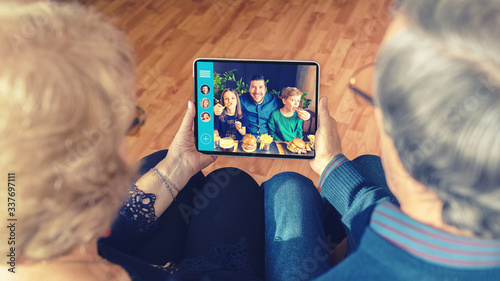 Obraz Senior couple chatting on video call with son and grandchildren due to home isolation quarantine - fototapety do salonu