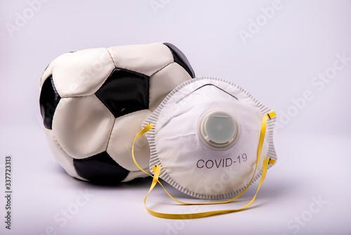 in the foreground a protective mask and a deflated soccer ball to symbolize the suspension of the soccer field in Italy and Europe as a preventive measure during the risk of coronavirus infection Canvas Print