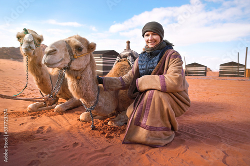 Photo Young woman in traditional Bedouin coat - bisht - and headscarf crouching next t