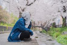 小川と桜と女性