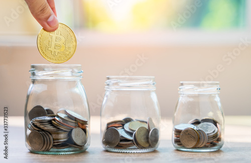 Fototapeta Money savings concepts hand holding bitcoin to put with coins in glass bottles to spend on expenses such as savings, tourism, investment, emergency, retirement on wooden table with blur background. obraz