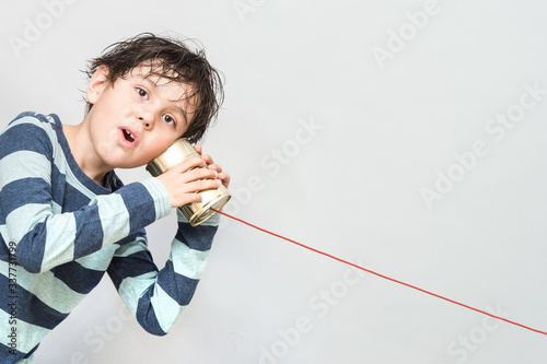 Fotografiet Little boy holding a can with a cord