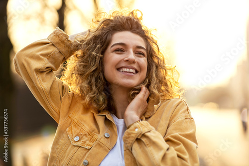 Obraz Portrait of young woman with curly hair in the city  - fototapety do salonu