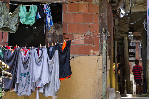 Fotografia Clothes hung up to dry on clothesline in front of a rundown bare house in Santa Marta favela in Rio de Janeiro, Brazil