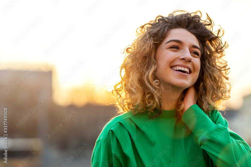 Fototapeta Portrait of young woman with curly hair in the city