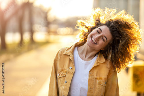 Portrait of young woman with curly hair in the city Slika na platnu