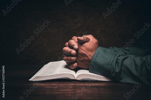 Fotografía Hands of a man praying over an open bible