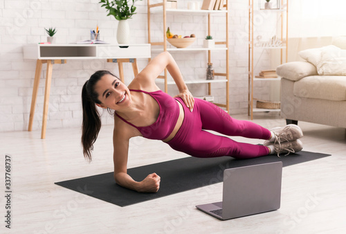 Fototapeta Sporty lady working out at home with online fitness course obraz