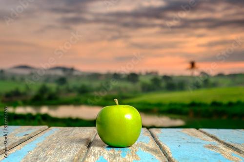 Fotografia Granny Smith Apple On Table Against Sky During Sunset