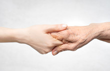 Helping Hand For The Elderly Concept With Young Hand Holding Old Hand.