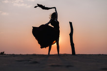 Girl In The Desert At Sunset In A Red Dress Developing In The Wind