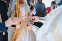 The Priest Holds A Wedding Ceremony In The Church, Rites And Puts Gold Rings On The Fingers Of The Newlyweds. Photography, Concept.