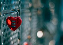 Close-up Of Heart Shape Padlock Hanging On Metal