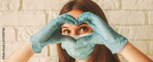 obraz dibond Banner young woman in protective face mask and medical gloves gesturing love shape sign. Happy girl in medical face mask and gloves looking through hands in form of heart symbol. Health care, COVID-19