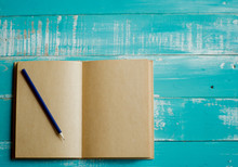 Pencil On Open Book At Table