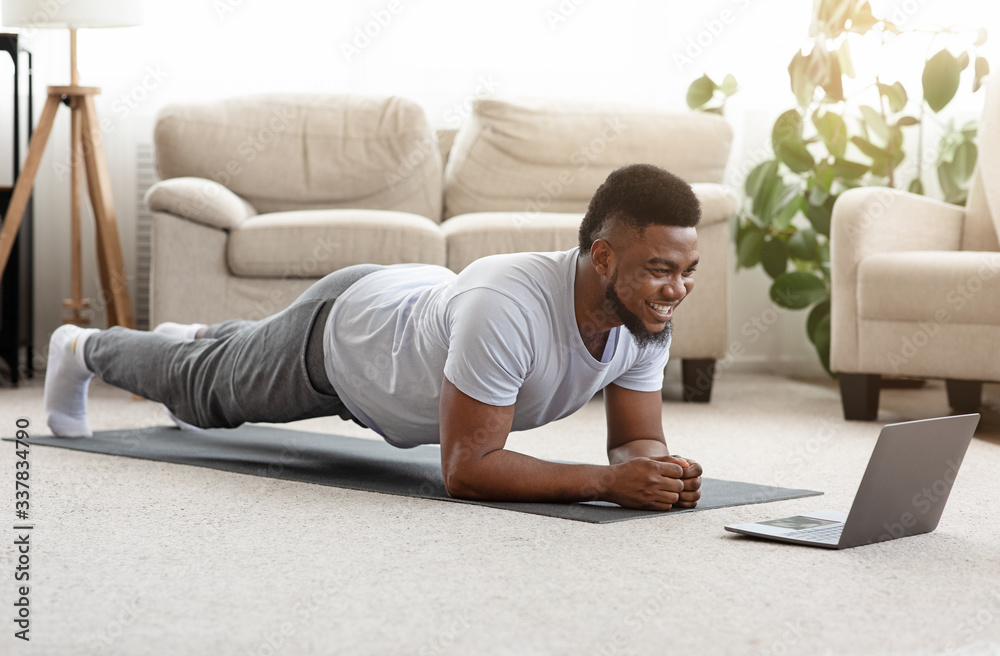 Fototapeta Sporty man training at home and watching online tutorial on laptop