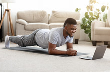 Sporty Man Training At Home And Watching Online Tutorial On Laptop