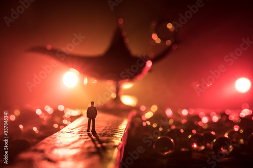 Silhouette of a man standing in the middle of the road on a misty night with giant Antique Aladdin arabian nights genie style oil lamp Canvas