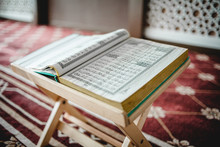 Close-up Of Open Koran On Table