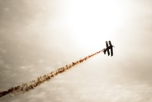 Low Angle View Of Silhouette Aerobatic Biplane With Vapor Trail Against Sky