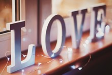 Close-up Of Illuminated String Light By Love Text On Window Sill