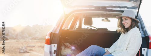 Fotografía Young traveling woman sitting in the trunk of a car and resting, chilling stop on the nature