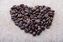 Close-up Of Roasted Coffee Beans In Heart Shape On Textile