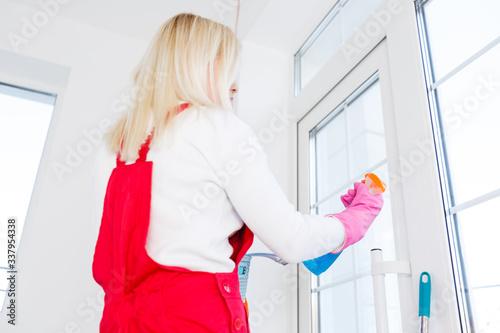 Fototapeta Beautiful young woman makes cleaning the house. Girl rubs dust. obraz na płótnie