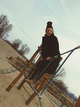 Smiling Young Woman Playing On Jungle Gym