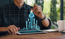 Business Start Up, Start, New Project Or New Idea Concept. Wooden Blocks With Launching Rocket Graphic Arrangedin Pyramidshape And A Man Is Holding The Top One.