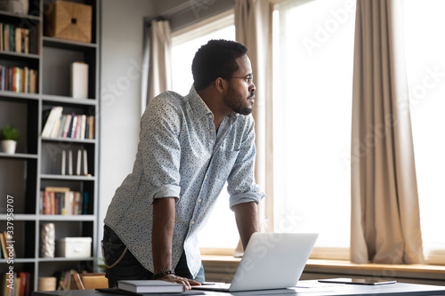 Papel de parede Young thoughtful african american businessman leaning on table with laptop, looking away