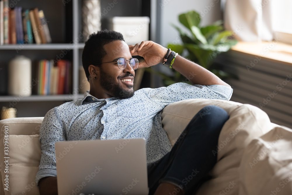 Fototapeta Happy young african american man stretching back, enjoying free leisure weekend time alone on sofa with computer. Smiling multiracial freelance guy distracted from job study, looking at window.