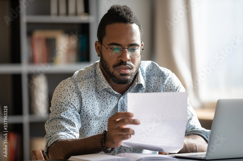 Fotografía Focused serious millennial african american businessman in glasses reading bank loan payment notification paper, sitting at table with computer