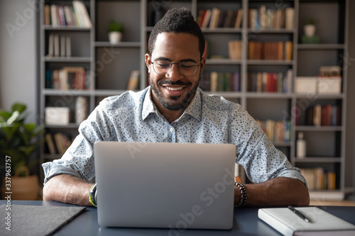 Fototapety, obrazy: Front view head shot young smiling african american businessman in eyewear looking at laptop screen, reading pleasant messages in social networks, working on computer sitting at table in office home.