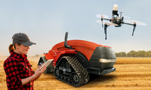 Woman Farmer With Digital Tablet Controls An Autonomous Tractor And Drone On A Smart Farm