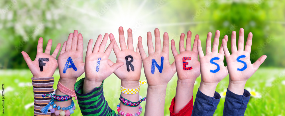 Fototapeta Children Hands Building Colorful Word Fairness. Sunny Green Grass Meadow As Background