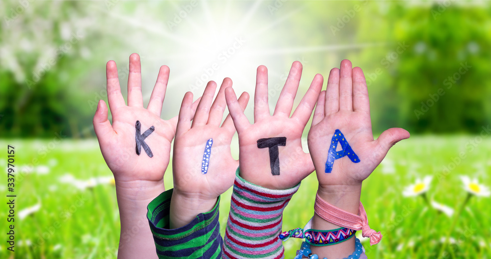 Fototapeta Children Hands Building Colorful German Word KITA Means Kindergarden. Sunny Green Grass Meadow As Background