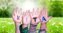 Children Hands Building Colorful German Word KITA Means Kindergarden. Sunny Green Grass Meadow As Background