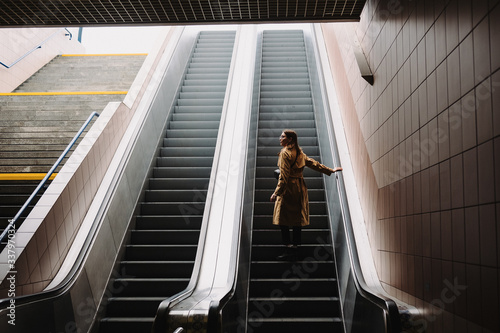 Beautiful young woman in trench coat stands on an escalator in the subway Tableau sur Toile