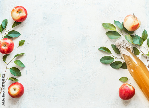 Photographie Bottle with homemade apple cider vinegar with apples and green leaves on white background