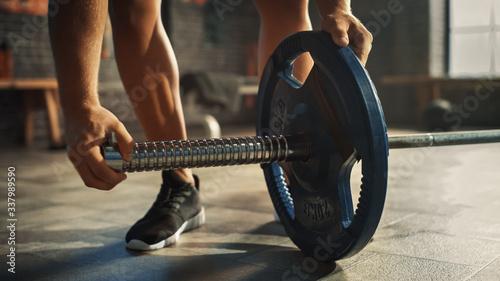 Fotografia, Obraz Close-up Shot of Bodybuilder Puts Additional Weights on a Barbell