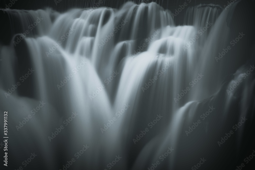 Fototapeta Greyscale closeup shot of the pouring foamy cascades of a waterfall