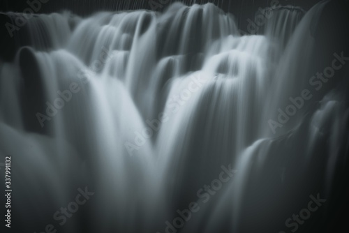 Fototapeta Greyscale closeup shot of the pouring foamy cascades of a waterfall obraz