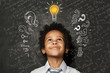 Smart kid with lightbulb. Brainstorming and idea concept. Little cute student boy on chalkboard background