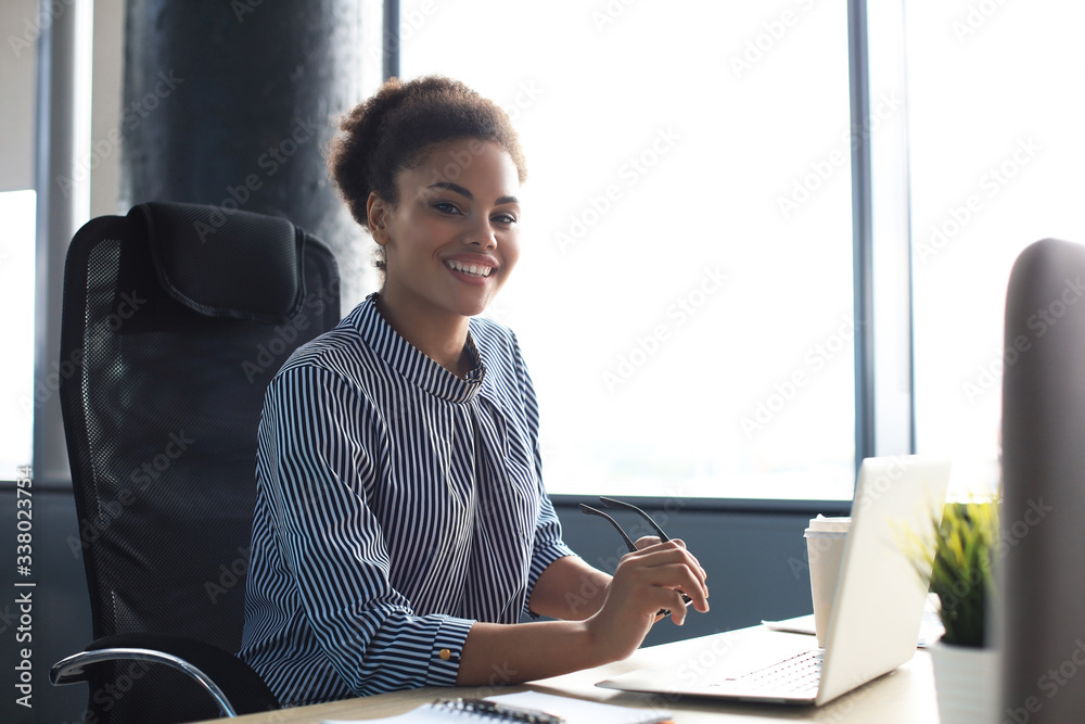 Fototapeta Portrait of beautiful young african american woman working with laptop while sitting at the table.