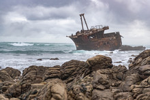 Shipwreck In Sea Against Cloudy Sky